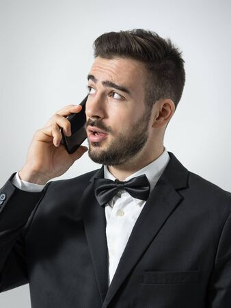 young unshaven: Young unshaven upset businessman on the phone looking up. Portrait over gray studio background.