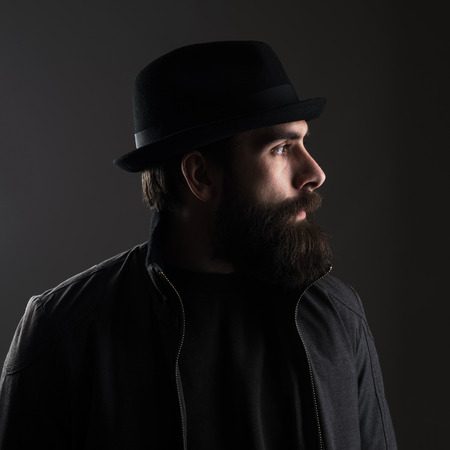 black hat: Profile view of bearded man wearing hat looking away. Low key dark shadow portrait over black background.