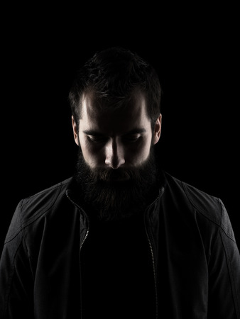 Sad bearded man looking down. Low key dark shadow portrait isolated over black background.