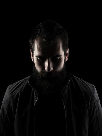 viso uomo: Triste uomo con la barba guardando in basso. Chiave di basso ritratto ombra scura isolato su sfondo nero.
