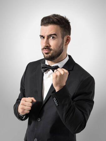 anillo de boda: Expresión divertida de nuevo el novio tomados apretó el puño gesto con el anillo de boda. Retrato sobre fondo gris de estudio. Foto de archivo