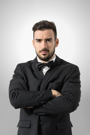 Angry bossy man in tuxedo with crossed arms intense looking at camera. Portrait over gray studio background. Foto de archivo