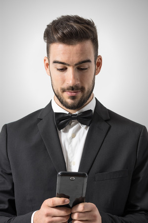 touch screen: Young man in tuxedo with bow tie holding mobile phone texting message. Portrait over gray studio background.