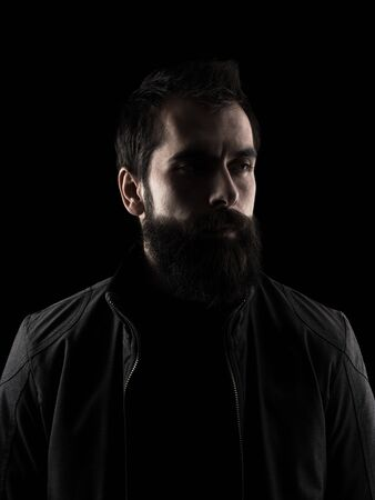 black shadow: Desaturated serious bearded hipster looking away. Low key dark shadow portrait isolated over black background.