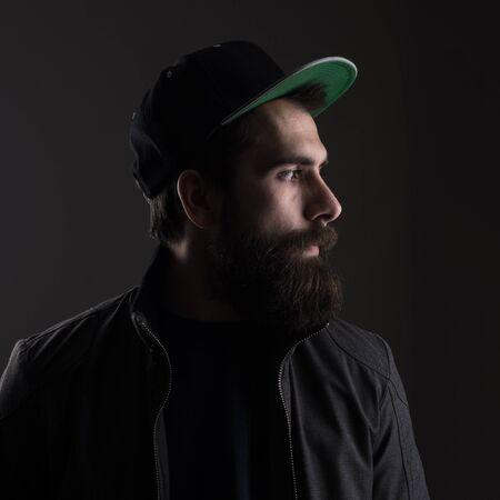 Sad man wearing baseball cap looking away. Low key dark shadow portrait over black background. Stock Photo
