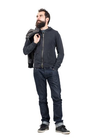 shoulder carrying: Serious hipster in hooded sweatshirt carrying jacket over the shoulder looking away. Full body length portrait isolated over white studio background.