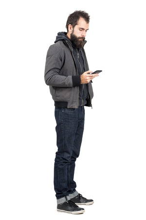 hooded sweatshirt: Young hipster wearing jacket over hooded sweatshirt typing on mobile phone.  Full body length portrait isolated over white studio background.