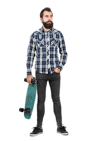 tight body: Confident hipster carrying skateboard in one hand looking away. Full body length portrait isolated over white studio background.