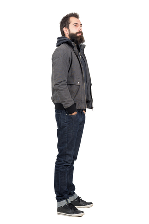 man profile: Side view of bearded man wearing jacket over hooded shirt looking away. Full body length portrait isolated over white studio background.