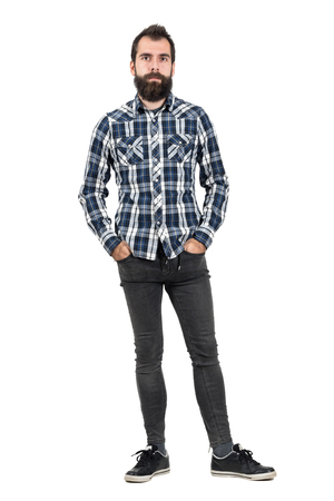 bearded: Confident serious hipster in plaid tartan blue shirt with hands in pockets. Full body length portrait isolated over white studio background.