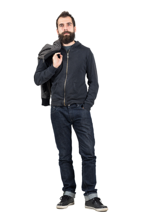 hooded sweatshirt: Serious hipster in hooded sweatshirt carrying jacket over the shoulder looking at camera. Full body length portrait isolated over white studio background.