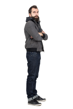 hooded sweatshirt: Profile view of bearded man wearing jacket over hooded sweatshirt with crossed arms looking at camera. Full body length portrait isolated over white studio background. Stock Photo