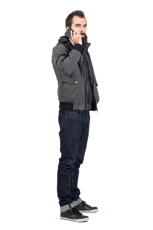 hooded sweatshirt: Serious bearded man in jacket and hooded sweatshirt talking on the cellphone looking at camera.  Full body length portrait isolated over white studio background.