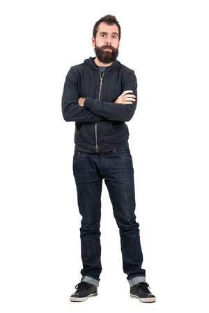 white men: Skeptical hipster in black hooded sweatshirt with crossed arms looking at camera. Full body length portrait isolated over white studio background. Stock Photo