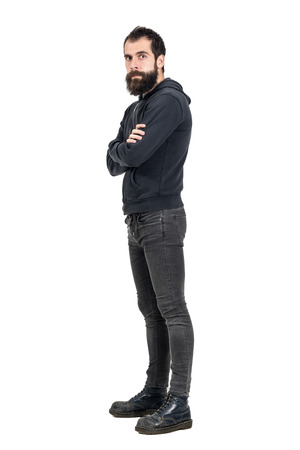 army boots: Confident serious punker wearing old worn boots and black hooded sweatshirt looking at camera. Full body length portrait isolated over white studio background. Stock Photo