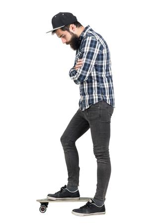 mani incrociate: Hipster con le braccia incrociate a guardare in piedi su skate board. Vista laterale. Tutto il corpo ritratto di lunghezza isolato su sfondo bianco studio.