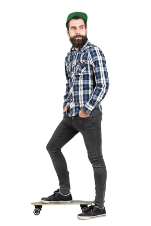longboard: Happy confident hipster with hands in pocket wearing baseball cap standing on longboard side view. Full body length portrait isolated over white studio background.