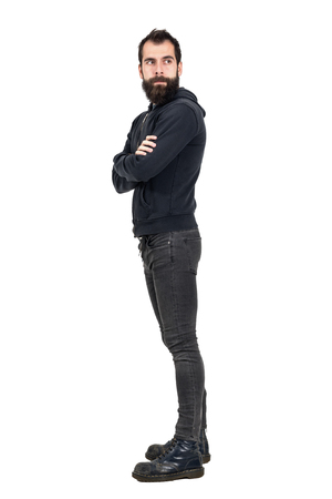 hooded sweatshirt: Side view of bearded punker wearing hooded sweatshirt with crossed arms looking away. Full body length portrait isolated over white studio background.