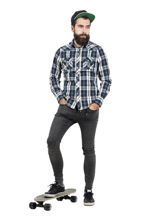 beard man: Confident bearded hipster with baseball cap standing on skate board looking down. Full body length portrait isolated over white studio background.