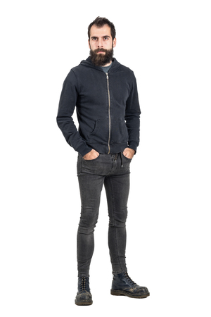 tight jeans: Tough confident stylish punker in black hooded sweatshirt looking at camera with hands in pockets. Full body length portrait isolated over white studio background.