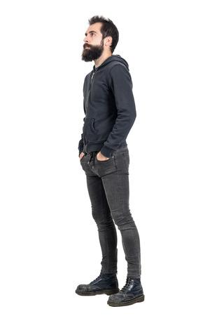 sudadera: Vista lateral de punk con barba o inconformista con las manos en los bolsillos mirando hacia arriba. la longitud del cuerpo Retrato completo aislado sobre fondo blanco del estudio.