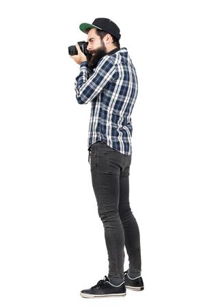 Zijaanzicht van hipster in plaid shirt en baseball cap nemen foto met dslr camera. Full body lengte portret geïsoleerd over witte studio achtergrond.