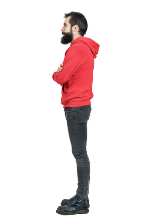 Side view of bearded young man in red hoodie with crossed arms looking away. Full body length portrait isolated over white studio background.