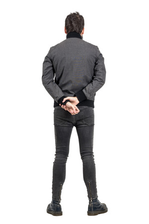 hands behind back: Rear back view of man in tight jeans and gray jacket looking away. Full body length portrait isolated over white studio background.