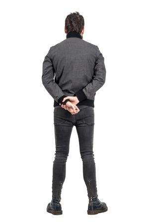 jeans apretados: vista posterior trasera del hombre en jeans ajustados y una chaqueta gris que mira lejos. la longitud del cuerpo Retrato completo aislado sobre fondo blanco del estudio.