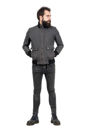 jeans apretados: punk barba grave en la chaqueta gris, jeans ajustados y botas del ejército de edad mirando a otro lado. la longitud del cuerpo Retrato completo aislado sobre fondo blanco del estudio.