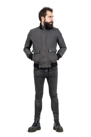 fashion style: Serious bearded punker in gray jacket, tight jeans and old army boots looking away. Full body length portrait isolated over white studio background.