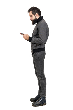 Zijaanzicht van stijlvolle bebaarde hipster typen op zijn smartphone. Het volledige portret van de lichaamslengte dat over witte studioachtergrond wordt geïsoleerd.