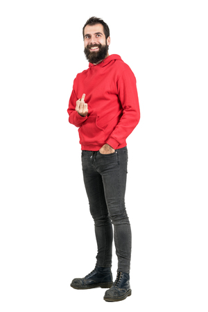 unkind: Laughing rebellious punker in red hoodie showing middle finger to camera. Full body length portrait isolated over white studio background.
