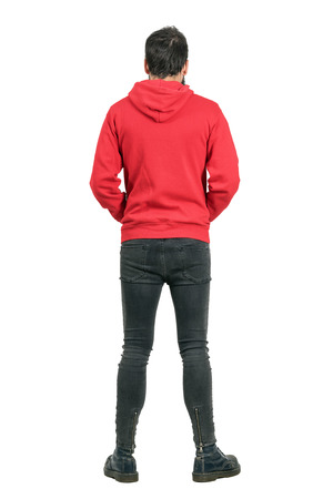 Achteraanzicht van de jonge man in strakke jeans en laarzen dragen van rode hoodie. Full body lengte portret geïsoleerd op een witte achtergrond studio.