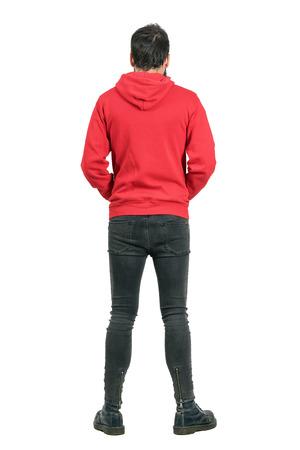 Vue arrière d'un jeune homme en jeans et des bottes étanches portant capuche rouge. corps plein longueur portrait isolé sur fond blanc studio. Banque d'images