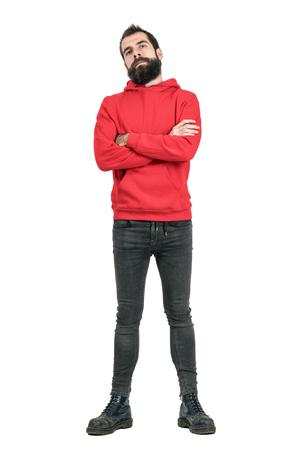 Trotse vertrouwde bearded man in rode hoodie met gekruiste armen naar camera kijken. Full body lengte portret geïsoleerd over witte studio achtergrond.