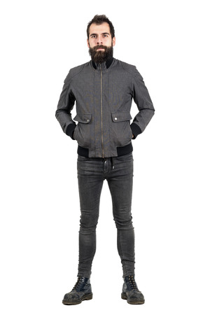 tight jeans: Confident bearded hipster in gray jacket, tight jeans and army boots looking at camera. Full body length portrait isolated over white studio background.