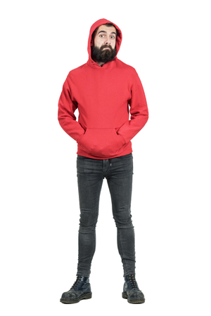 uomo rosso: espressione divertente del punk con la barba confusa con le mani in tasca guardando a porte chiuse. Tutto il corpo ritratto di lunghezza isolato su sfondo bianco studio. Archivio Fotografico