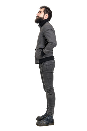 tight body: Side view of young bearded punker in old army boots looking up with hands in pockets. Full body length portrait isolated over white studio background. Stock Photo