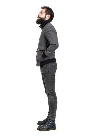 jeans apretados: Vista lateral de punk joven con barba en las botas del ejército de edad mirando hacia arriba con las manos en los bolsillos. la longitud del cuerpo Retrato completo aislado sobre fondo blanco del estudio. Foto de archivo