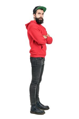 Vue de côté d'un jeune homme barbu à capuche rouge coiffé d'une casquette de base-ball, les bras croisés. corps plein longueur portrait isolé sur fond blanc studio.