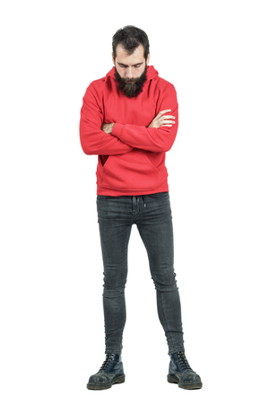 hooded sweatshirt: Bearded man with crossed arms in red hooded sweatshirt looking down. Full body length portrait isolated over white studio background.