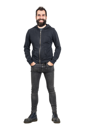 army boots: Laughing bearded punker in black hoodie with hands in pockets looking at camera. Full body length portrait isolated over white studio background. Stock Photo