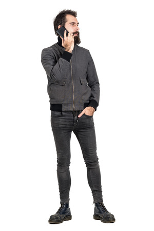 jean: Cool confident serious hipster wearing gray jacket and military boots talking on the cellphone looking away. Full body length portrait isolated over white studio background.