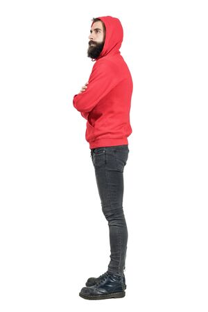 hooded sweatshirt: Side view of young bearded man in red hooded sweatshirt with crossed arms looking away. Full body length portrait isolated over white studio background.