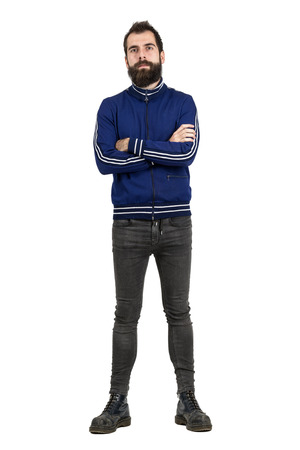 tracksuit: Confident proud bearded man in blue tracksuit jacket and tight jeans looking at camera with crossed arms. Full body length portrait isolated over white studio background.