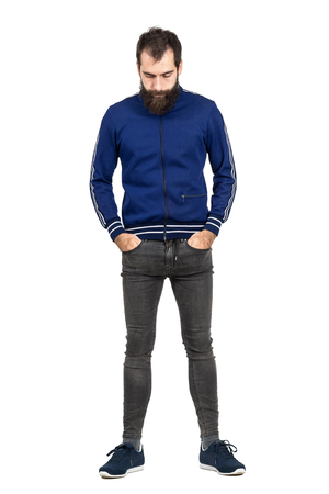 pocket: Bearded hipster in retro clothes with hands in pockets looking down. Full body length portrait isolated over white studio background.