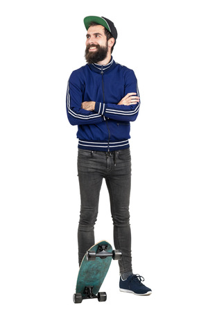 tracksuit: Young hipster in blue tracksuit jacket and baseball cap on skateboard looking away smiling. Full body length portrait isolated over white studio background.