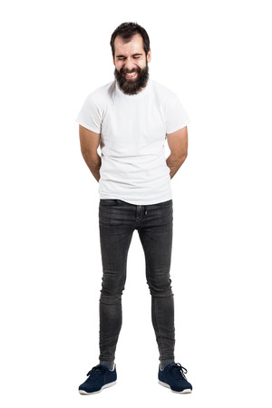 spontaneous expression: Spontaneously laughing bearded man with hands on back in white t-shirt. Full body length portrait isolated over white studio background.