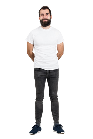 eccentric: Happy bearded man with hands behind back in white t-shirt and tight jeans looking at camera. Full body length portrait isolated over white studio background.